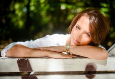 Pretty Woman Leaning on a Bench at the Park Royalty Free Stock Image