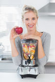 Pretty woman leaning on her juicer full of fruit and holding red Stock Photos