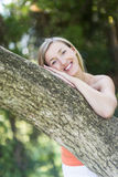 Pretty woman leaning on a tree trunk. Pretty young blond woman leaning on a tree trunk in a park or garden smilng at the camera in contentment Royalty Free Stock Image