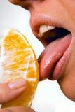 Pretty woman licking orange slice Stock Photography