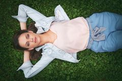 Pretty woman lies on grass royalty free stock images