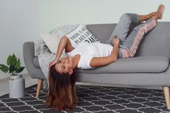 Beautiful woman relaxing on a grey couch with head upside down. Cute girl having fun at cozy home in lazy day. stock image