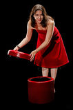 Pretty woman lifting the cover of a redd footstool Stock Photography