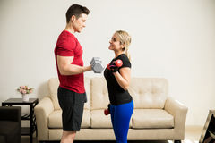 Pretty woman lifting weights with her boyfriend Royalty Free Stock Photos