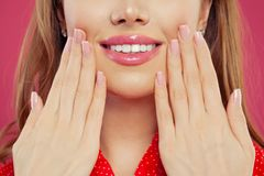 Pretty woman lips and hand with manicured nails. Pink nail polish and makeup lips with natural pink color lipgloss.  stock images