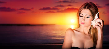 Pretty woman listen to the seashell to the sunset Royalty Free Stock Photos