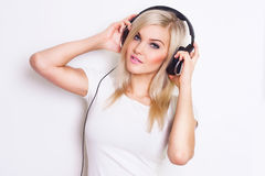 Pretty woman listening and enjoying music in headphones. Royalty Free Stock Images