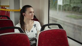 Pretty woman listening music in headphones on smartphone riding train, beautifull girl rides a city bus. Public transport stock video