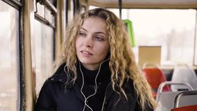 Pretty woman listening music in headphones on smartphone riding tram.  stock footage