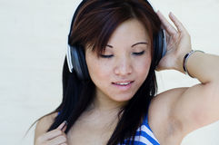 Pretty woman listening to music with headphones Stock Photography