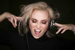 Pretty woman listening to music via headphones and sing stock images
