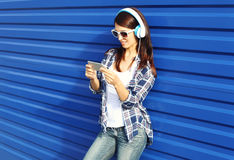 Pretty woman listens to music in headphones and using smartphone Royalty Free Stock Photo