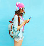 Pretty woman listens to music in headphones using smartphone over blue background Stock Photos