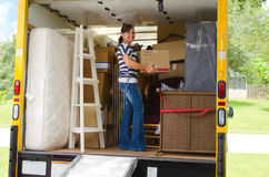Pretty woman loading a full moving truck. A pretty woman with a box in her hands is loading a very full moving truck Royalty Free Stock Images