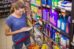 Pretty woman looking at her grocery list Royalty Free Stock Photo