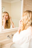 Pretty woman looking at herself in the mirror. In the bathroom royalty free stock photo