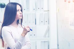 Pretty woman looking at office whiteboard Stock Image
