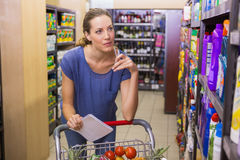 Pretty woman looking at product on shelf and holding grocery list Stock Photo