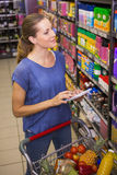 Pretty woman looking at product on shelf and holding grocery list Stock Photos
