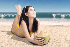 Pretty woman looking something on beach. Pretty woman looking something while lying with a coconut drink on the beach Royalty Free Stock Photos