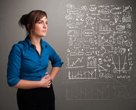 Pretty woman looking at stock market graphs and symbols Stock Photography