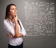 Pretty woman looking at stock market graphs and symbols Stock Photos