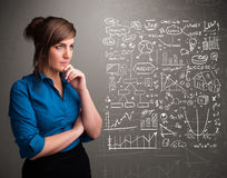 Pretty woman looking at stock market graphs and symbols Royalty Free Stock Image