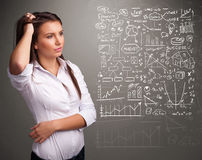 Pretty woman looking at stock market graphs and symbols Stock Images