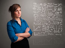 Pretty woman looking at stock market graphs and symbols Royalty Free Stock Images