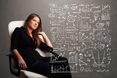 Pretty woman looking at stock market graphs and symbols Stock Photos