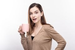 Pretty woman looking surprised by taste of coffee. Surprising taste. Charming young woman holding a cup of coffee and looking at the camera with surprised Royalty Free Stock Photos