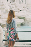 Pretty woman looking to the fountain of Trevi during her trip in Royalty Free Stock Image