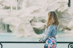 Pretty woman looking to the fountain of Trevi during her trip in Stock Image