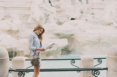 Pretty woman looking a touristic map near the fountain of Trevi Stock Images