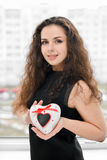 Pretty woman in love holding heart-shaped box Stock Image