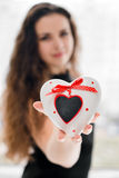 Pretty woman in love holding heart-shaped box Royalty Free Stock Images