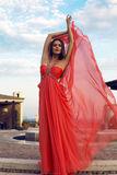 Pretty woman in luxurious red dress posing at park Royalty Free Stock Photos