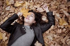 Pretty woman is lying in autumn park on fallen leaves. Beautiful landscape at fall season royalty free stock images