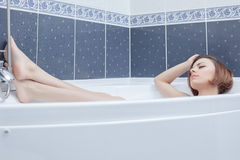 Pretty woman lying in bath Stock Photos