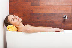 Pretty woman lying in bath. Pretty woman lying in white bath and relaxing Royalty Free Stock Photography