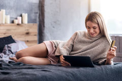 Pretty woman lying in bed with laptop and shopping