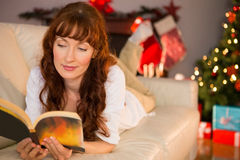 Pretty woman lying on a cosy couch reading book Royalty Free Stock Image