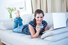 Pretty woman lying on couch doing online shopping Royalty Free Stock Images