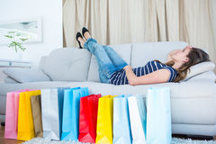 Pretty woman lying on couch near shopping bags. In living room Stock Photography