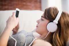 Pretty woman lying on the couch using her phone and listening music Royalty Free Stock Images