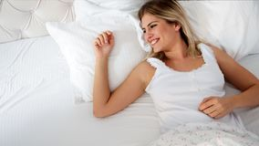 Pretty woman lying down on bed at home Royalty Free Stock Photography