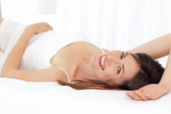 Pretty woman lying down on her bed Royalty Free Stock Photography