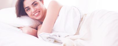 Pretty woman lying down on her bed at home royalty free stock images