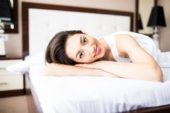 Pretty woman lying down on her bed at home in the morning Royalty Free Stock Image