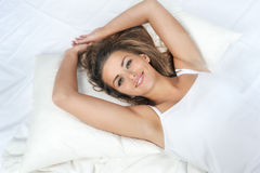 Pretty woman lying down on her bed at home Royalty Free Stock Photo
